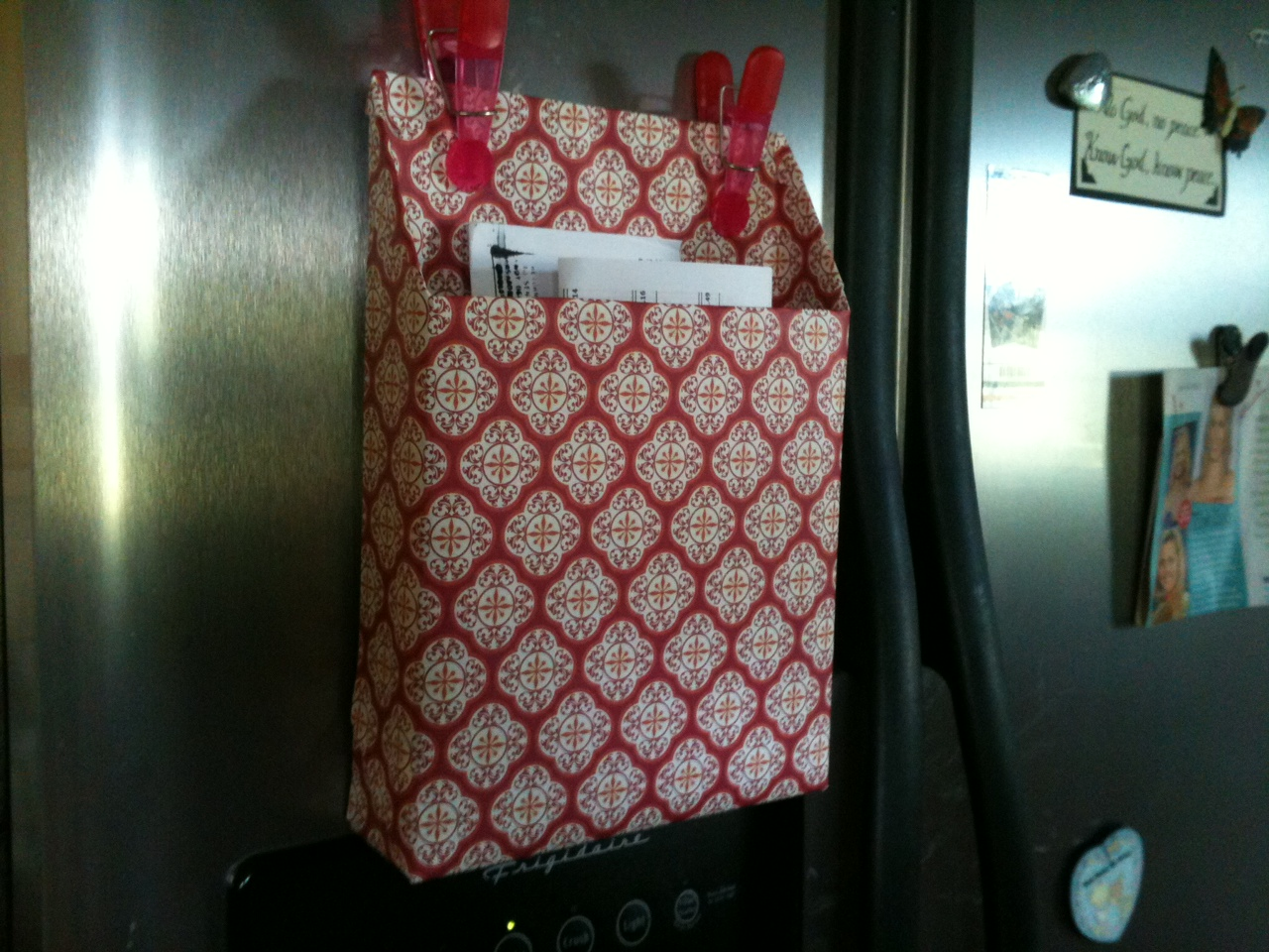 Cereal box covered in scrapbook paper with magnets on the side of the fridge. Gr