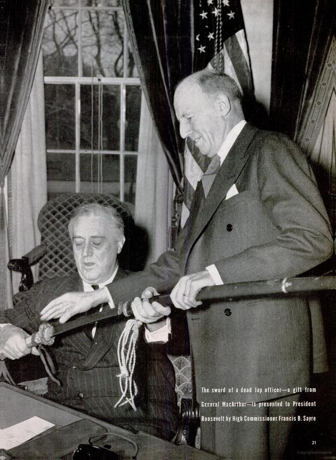 """Caption from LIFE magazine: """"The sword of a dead Jap officer a gift from Ge"""