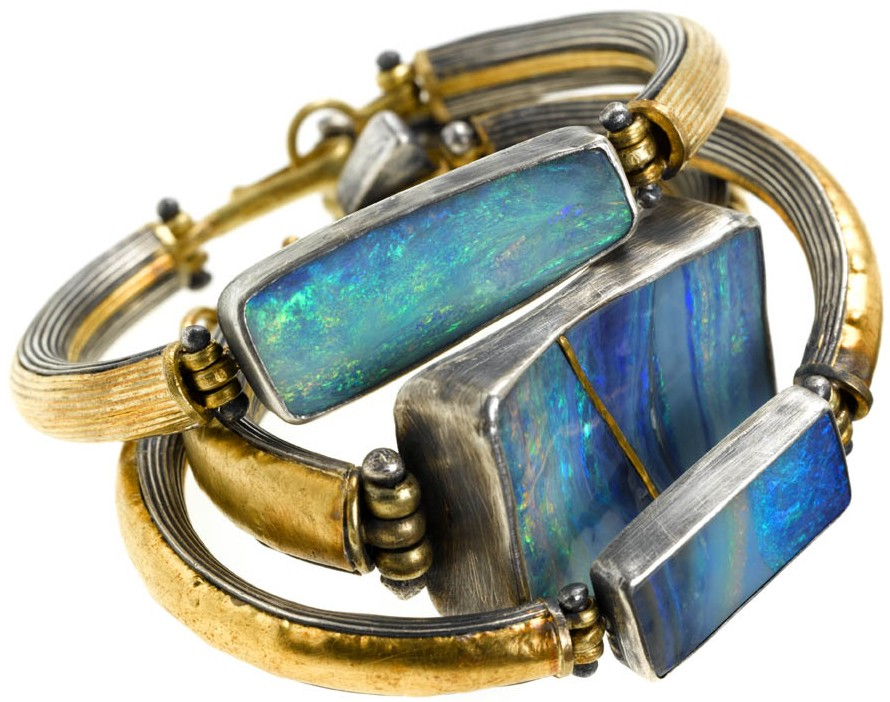 Opals set in bracelets with silver and gold by Judy Geib. Look close at the repa
