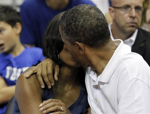President Barack Obama, right, kisses first lady Michelle Obama for the 'Kis