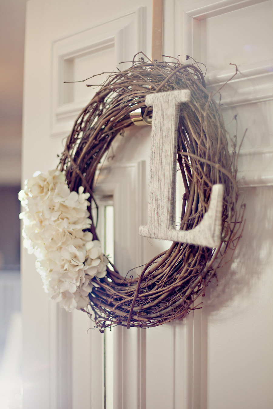 Use a grapevine wreath with sweet white flowers and a white washed initial for a