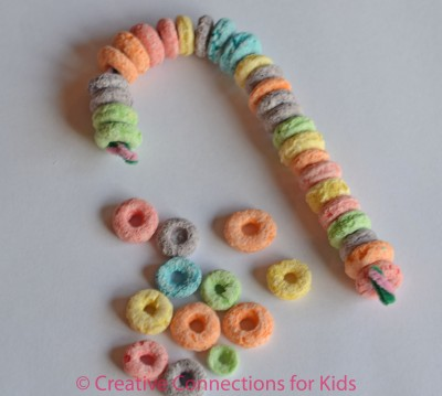 Cereal Candy Cane Tree Decoration- Child strings cheerios or fruit loops onto pi