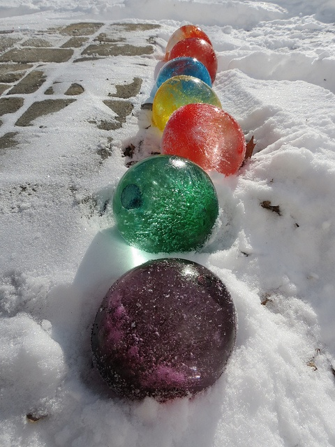 During winter fill balloons with water and add food coloring, once frozen cut th
