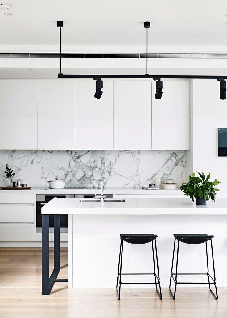 Black and white monochrome kitchen: handleless white cabinets and benchtops, grey marble splashback, black bar stools, black